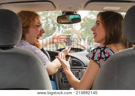 Man and woman funny couple arguing in car having relationship problem yelling at each other.