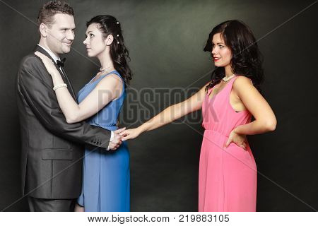 Love triangle concept. Man cheating on his wife looking and touching other woman choosing between two ladies.