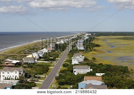 Distant aerial view of Oak Island NC coastal living homes road marsh and more in the summer. Day high view of homes and more at Atlantic coasts Oak Island.