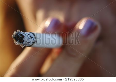 the girl drags on a cigarette. the harm of Smoking to the human body.