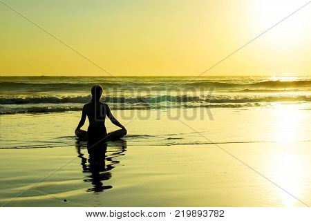 silhouette of unknown unrecognizable woman sitting on beach sea water practicing yoga and meditation looking to the sun on the horizon with an amazing beautiful orange sunset sky