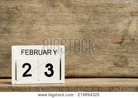 White block calendar present date 23 and month February on wood background