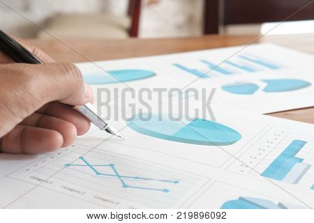Business analyst - hand with pen, calculator, sheet and graph from top view.