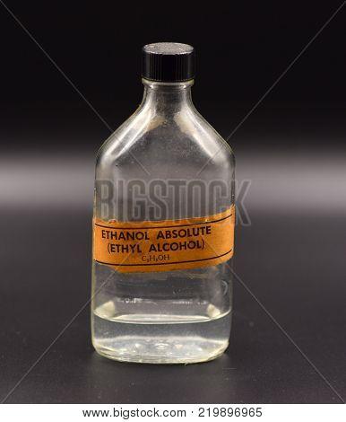 Vintage ethanol (ethyl-alcohol) bottle on a seamless black background.
