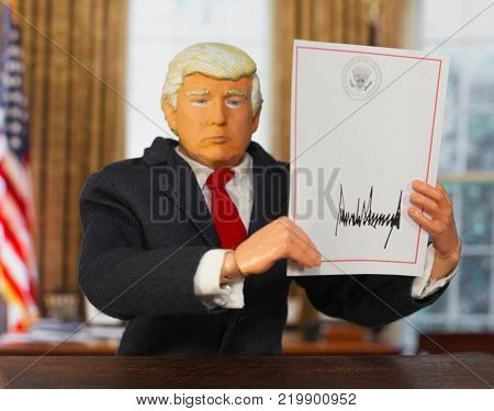 Caricature of United States President Donald Trump holding up a blank signed executive order
