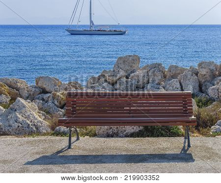 Empty wooden bench at boat dock with beautiful blue sea and docked boat in the background