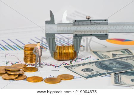Miniature business man and vernier measuring money coin on business chart business concept.