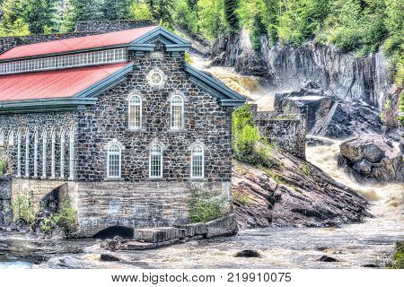 Chicoutimi, Canada - June 3, 2017: La Pulperie de Chicoutimi Regional Museum Pulp mill in Saguenay, Quebec with river and water flowing in summer