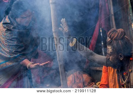 BABUGHAT KOLKATA WEST BENGAL / INDIA - 11TH JANUARY 2015 : Hindu Sadhu with white ash applied on body and face blessing sari clad Indian devotee woman.