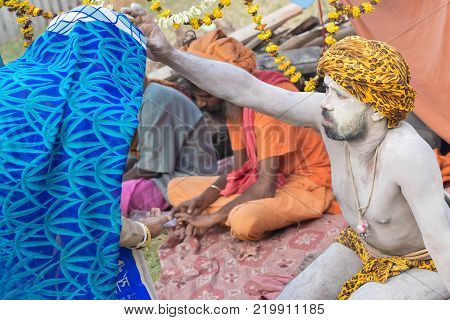 BABUGHAT KOLKATA WEST BENGAL / INDIA - 10TH JANUARY 2015 : Hindu Sadhu with white ash applied on body and face blessing blue sari clad Indian devotee woman.