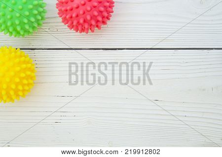Pet care, veterinary, grooming concept. A white wooden background with a corner of pet toys - colorful rubber squeaky balls. Space for your your text or product display.
