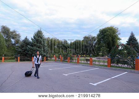In Parking Goes Young Man Arabic Attractive Appearance With Beard and Dark Hair Dressed in Suit Black Pants White Shirt With Black Sweater on Shoulders and Roll Black Suitcase Laggage in His Hand. Concept of Business Trip, Business Meeting, Travel, Busine