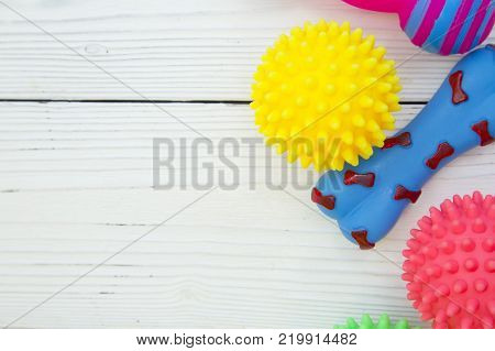 Pet care, veterinary, grooming concept. Pets having fun. A white wooden background with a rubber squeaky toys- balls and bones. Space for your text or image.