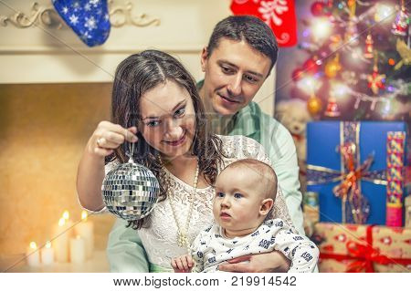 Father mother and child near the New Year tree. The child is looking at the mirror ball.