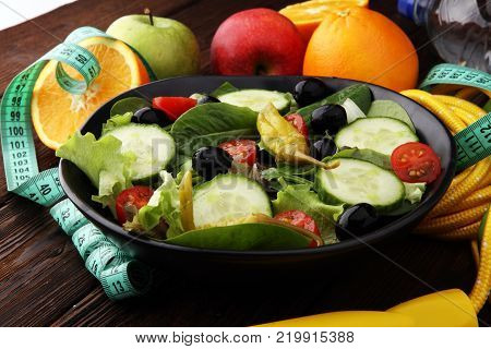 Fitness concept with salad bowl dumbbells skipping rope bottle water apples and tape measure