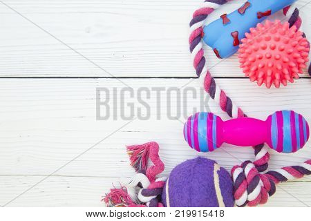 Pet care, veterinary, grooming concept. Pets having fun. A white wooden background with colorful textile and rubber pet toys- bones, balls and twisted rope . Space for your text or image.