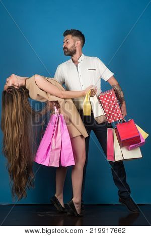 Black Friday happy holiday relations. Girl and bearded man hold present pack cyber Monday. Shopping and sale. Fashion shopaholic couple. Couple in love hold shopping bag near blue wall.
