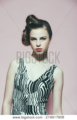 Beauty and fashion cosmetics. Woman with retro hair and fashionable makeup pinup. Makeup hairdresser and cosmetics. Girl in stylish vintage dress on pink background. pinup youth and look.