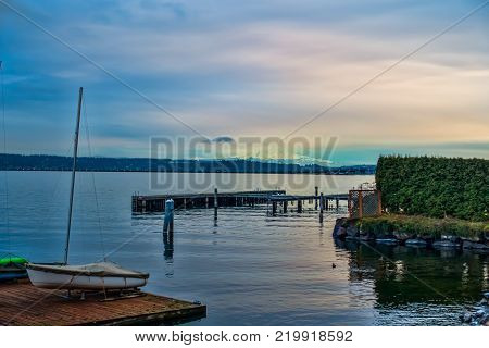 A view of a pier on Lake Washington with a cloud-covered Mount Rainier in the distance.