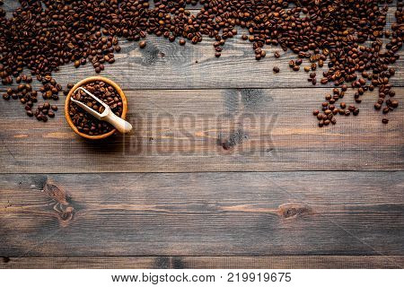 Fresh roasted coffee beans in bowl and scoop on dark wooden table top view copyspace. Coffee background