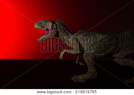 allosaurus with spot light on the head and red light on background