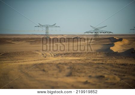 Power line towers in desert on blue sky background. Electricity distribution stations. Electric energy transmission. Global warming climate change. Ecology eco power technology concept.