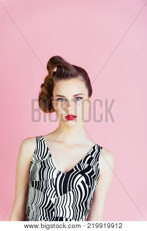 pinup youth and look. Makeup hairdresser and cosmetics. Girl in stylish vintage dress on pink background. Woman with retro hair and fashionable makeup pinup. Beauty and fashion cosmetics.