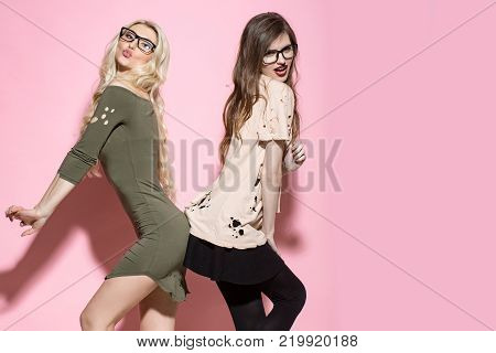 Girls pose in torn clothes on pink background. Beauty look concept. Fashion style vogue. Visage makeup hairstyle. Women with long hair in geek glasses copy space