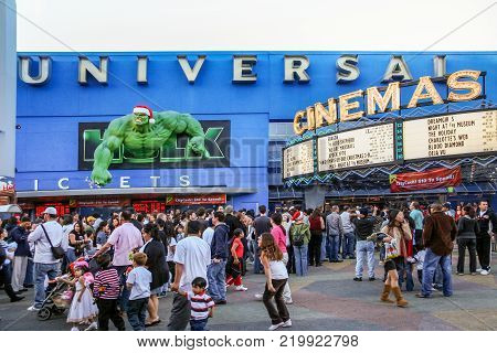 LOS ANGELES, CALIFORNIA, USA, DECEMBER 25, 2006 - Some people line up at the cinema box office inside Universal Studios in Hollywood just below a figure of a popular superhero dressed in a Christmas hat.