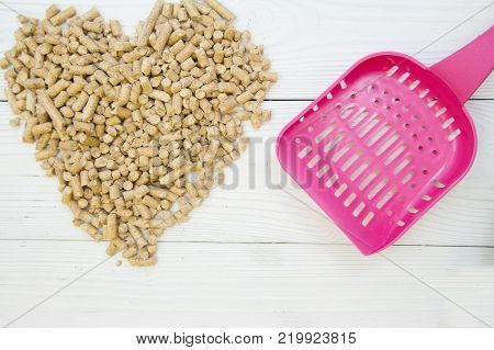 Pet care concept. A heart made of pet toilet filler and a pink toilet scoop. Wood filler for pets- cats, mice, rats, rabbits, hamsters. White wooden background.