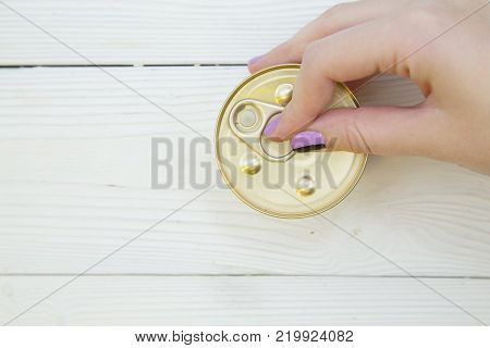Feeding your pet friend. A hand opening a tin can of pet food , close up. White wooden background. Pet shop banner. Space for your text or image.