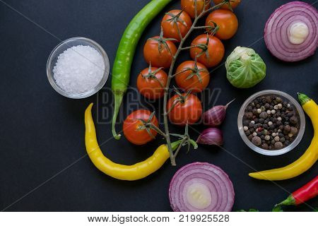 Traditional Latin American mexican Tomato sauce salsa, chilean chancho en piedra in stone mortar and ingredients tomatoes, chile, garlic, onion, dark slate stone background. Top view.