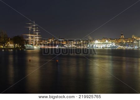 STOCKHOLM SWEDEN - DEC 27 2017: Nightscape of the beautiful sailing ship and hotel Af Chapman and a large ferry in central Stockholm in Sweden December 27 2017
