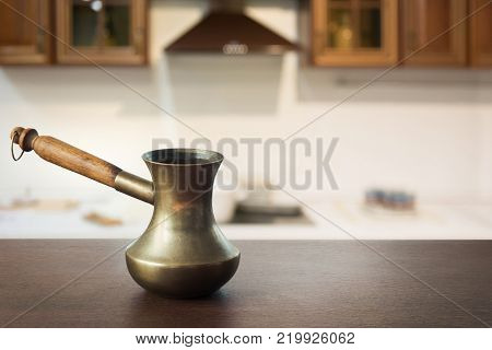 Vintage copper cezve with black coffee on wooden tabletop and defocused modern kitchen as background for display or montage your coffee products.