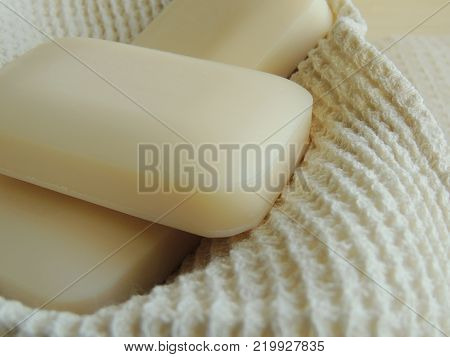 Bars of natural soap on white natural linen waffle texture towel.
