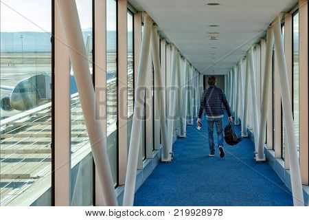 A man with a backpack in his hands walks down the corridor to board the plane. Out the window feed part of the aircraft.