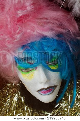 Head of a clothing store mannequin modeling pink and blue hair as well as green, yellow, purple and black makeup in a bed of shiny gold tinsel.