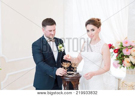 A beautiful happy couple in the registry office performs a wedding ritual with candle lighting. The concept of a happy marriage and marriage procession in the registry office.