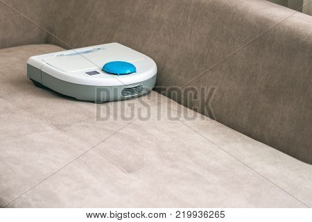 A modern robotic vacuum cleaner doing sofa. Automatic cleaning process