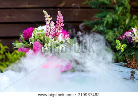 Beautiful decoration composition bouquet on a table and dry ice smoke.