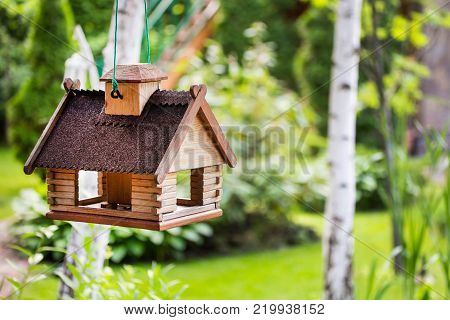 A feeder for birds made in a form of a house in a garden.