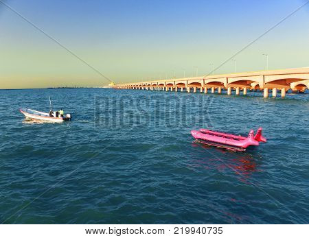 Small boat in side of a long arches dock in Progreso port, Yucatan , Mexico