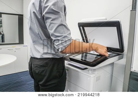 businessman press paper sheet on printer for copying and scanning documents