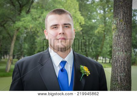 portrait of a headshot of a caucasian groom with a yellow boutonniere in his lapel