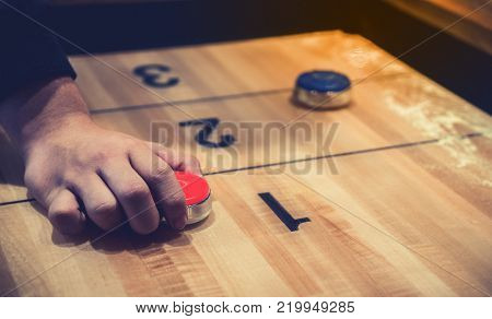 Vintage Shuffle Board Game With Red And Blue Disc And Hand Holding Red Blue Disc On Wooden Shuffle T