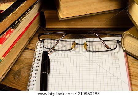 Notepad, Fountain Pen And Glasses In Front Of Books