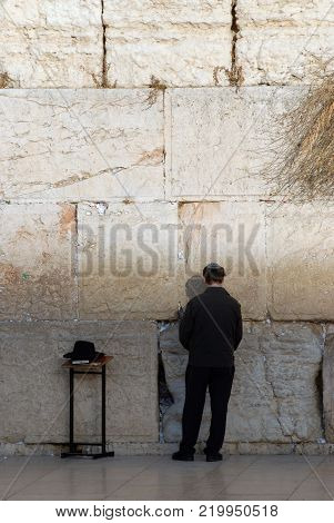 Man is a Jew in traditional Jewish national clothes and a pile near Ha-Kotel ha-Maaravi in Jerusalem, Israel.