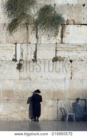 Man is a Jew in a traditional national black hat, a frock coat and stockings stands near the Western Wall, Ha-Kotel ha-Maaravi, Israel.