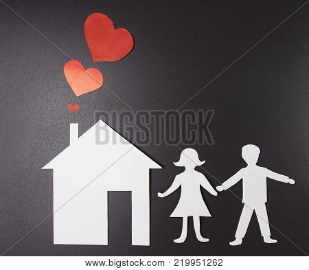 concept of happiness, family and home. Love in family. House and silhouettes of men and women of paper on black background. Red hearts from the chimney. symbol of love. Family and home insurance