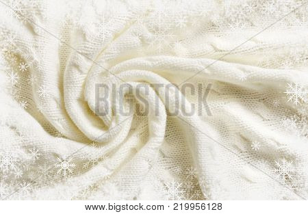 Folded white knitted plaid and snowflakes frame for winer or Christmas background. Flat lay. Top view.